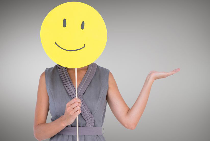 Image: woman covering face with happy face emoji