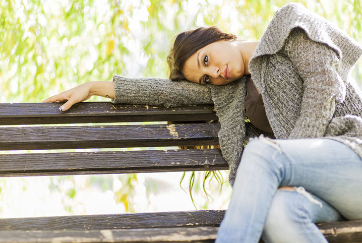 Depressed woman sitting on a bench