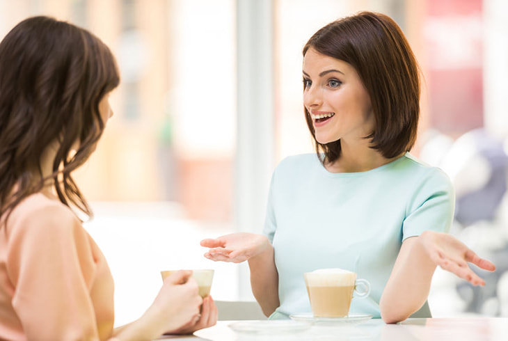 Two ladies talking while drinking coffee